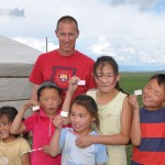 Jon gives Canadian flags and pencils to nomad family as they are in process of autumn set-up - Mongolia