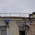 Precarious perch - workers repairing facade on building - Moscow