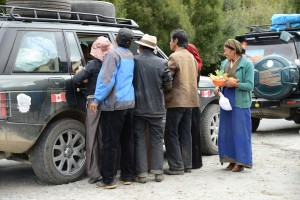 Crowd around ladies' car for giveaways - rural Tibet