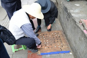 Men playing popular board game on sidewalk - Lhasa, Tibet